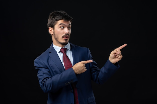 Front view of young emotional concentrated man in suit pointing up on isolated dark wall