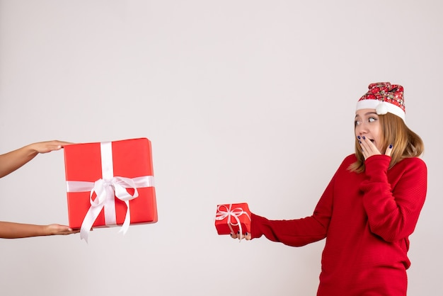 Giovane femmina di vista frontale che accetta un altro regalo di natale dalla donna