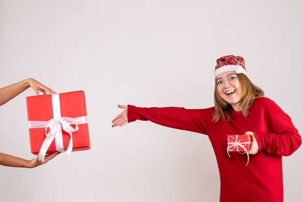 女性から別のクリスマスプレゼントを受け入れる正面図若い女性