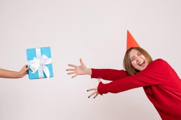 Вид спереди молодая женщина, принимая ее подарок