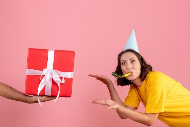 Вид спереди молодая женщина принимает подарок от мужчины на розовом столе, новогодняя эмоция, рождественская вечеринка, цвет женщины