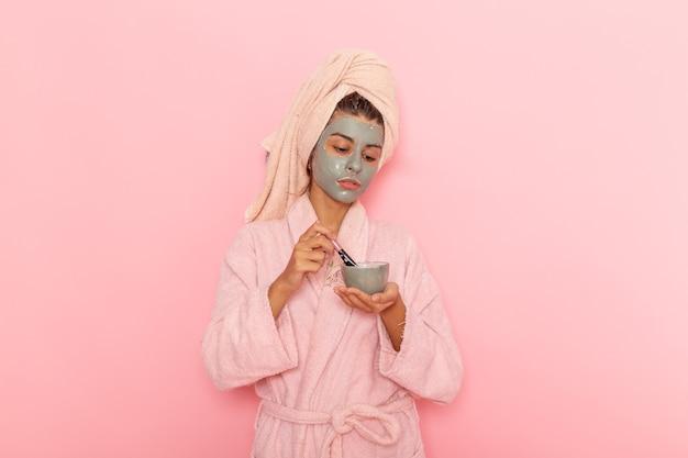 Вид спереди молодая женщина после душа в розовом халате, применяющая маску на розовом полу, ванна, душ, водный крем, девушка красоты
