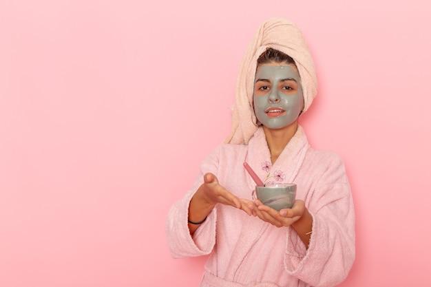 淡いピンクの表面にマスクを適用するピンクのバスローブでシャワーを浴びた後の正面図若い女性