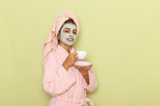 緑の表面でコーヒーを飲むピンクのバスローブでシャワーを浴びた後の正面図若い女性