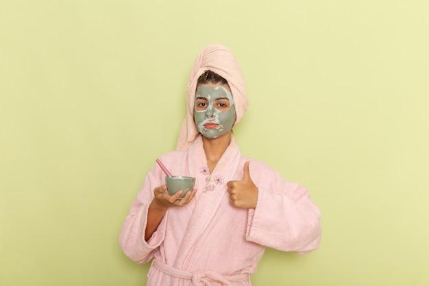Вид спереди молодой женщины после душа в розовом халате, держащей миску с маской на зеленой поверхности