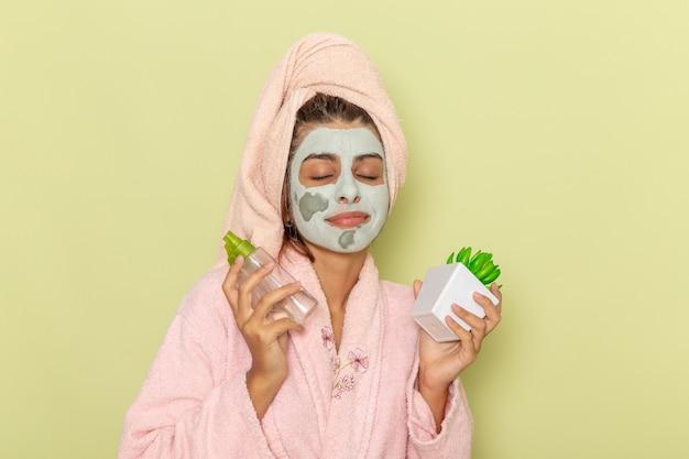 Вид спереди молодая женщина после душа в розовом халате, держащая средства для снятия макияжа на зеленом полу, крем-маска, душ, уход за собой, косметическая ванна