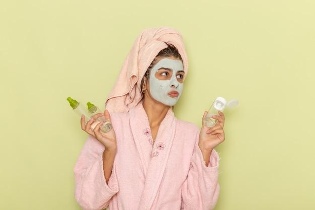 Вид спереди молодой женщины после душа в розовом халате, держащей средства для снятия макияжа на зеленой поверхности