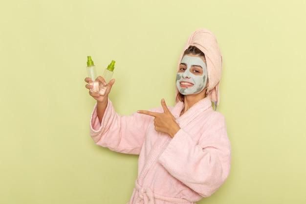 緑の表面に笑みを浮かべてメイク落としを保持しているピンクのバスローブでシャワーを浴びた後の正面図若い女性
