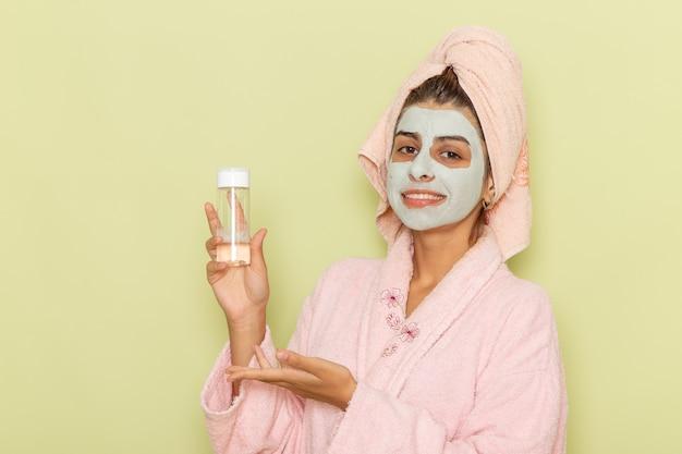 緑の机の上にスプレーと綿を保持しているピンクのバスローブでシャワーを浴びた後の正面図若い女性