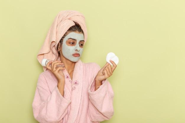緑の表面にスプレーと綿を保持しているピンクのバスローブでシャワーを浴びた後の正面図若い女性