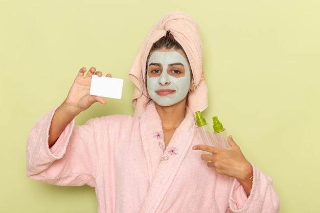 緑の表面にスプレーとカードを保持しているピンクのバスローブでシャワーを浴びた後の正面図若い女性