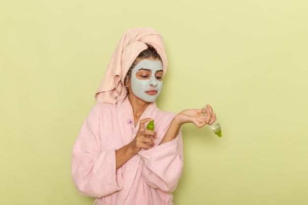 緑の表面にスプレーを保持しているピンクのバスローブでシャワーを浴びた後の正面図若い女性