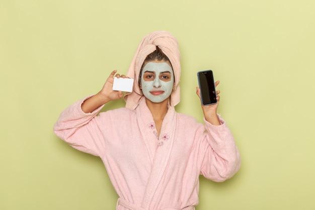 緑の机の上に白いカードと電話を保持しているピンクのバスローブでシャワーを浴びた後の正面図若い女性