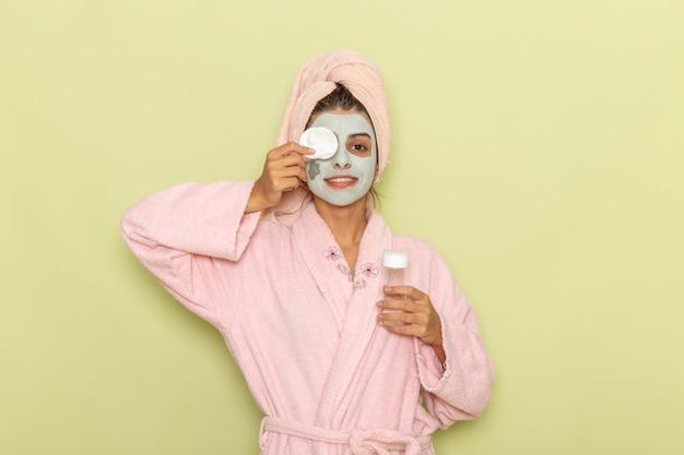Вид спереди молодая женщина после душа в розовом халате, снимая маску на зеленой поверхности