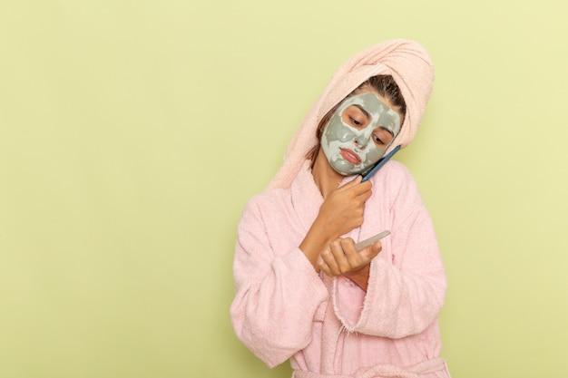 薄緑色の表面で電話で話しているピンクのバスローブでシャワーを浴びた後の正面図若い女性