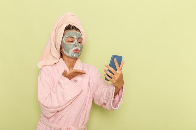 Вид спереди молодая женщина после душа в розовом халате, используя свой телефон на зеленой поверхности