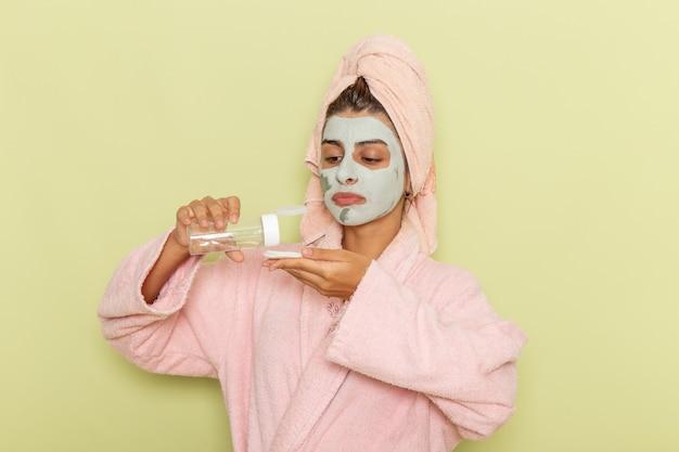 緑の表面にメイク落としを使用してピンクのバスローブでシャワーを浴びた後の正面図若い女性
