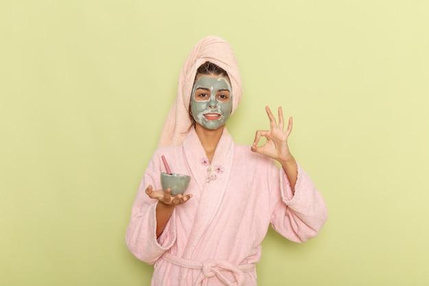 Giovane femmina di vista frontale dopo la doccia in ciotola rosa della tenuta dell'accappatoio con la maschera su una superficie verde