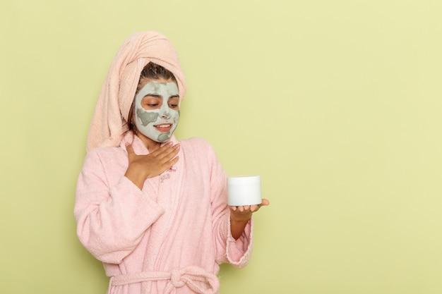 Giovane femmina vista frontale dopo la doccia in accappatoio rosa che tiene crema sulla superficie verde