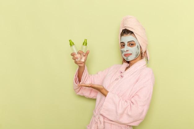 Giovane femmina di vista frontale dopo la doccia in accappatoio rosa che tiene gli struccanti sulla scrivania verde