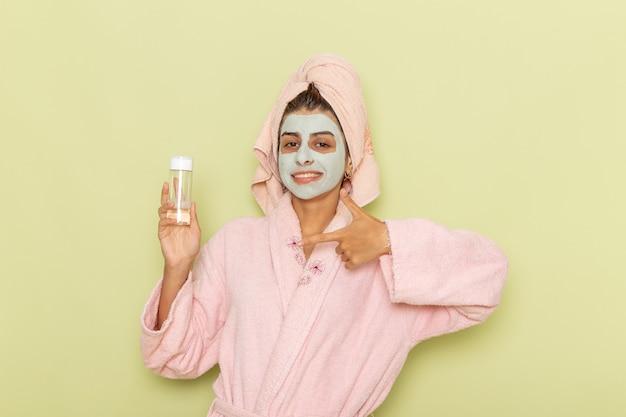 Giovane femmina di vista frontale dopo la doccia in accappatoio rosa che tiene spray su una superficie verde