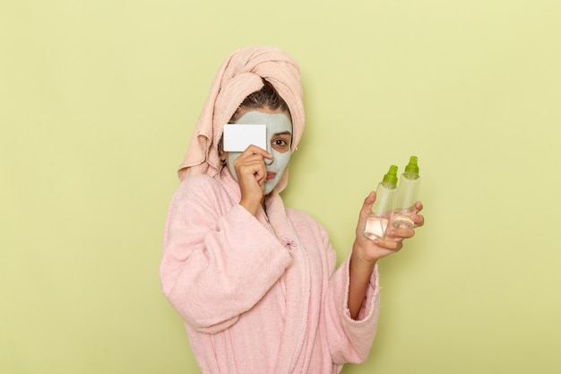 Giovane femmina di vista frontale dopo la doccia in accappatoio rosa che tiene gli spray e carta bianca sulla superficie verde