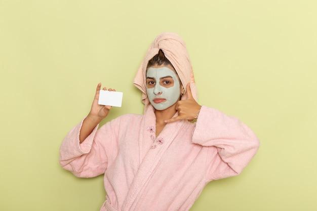 Giovane femmina di vista frontale dopo la doccia in accappatoio rosa che tiene carta bianca sulla superficie verde