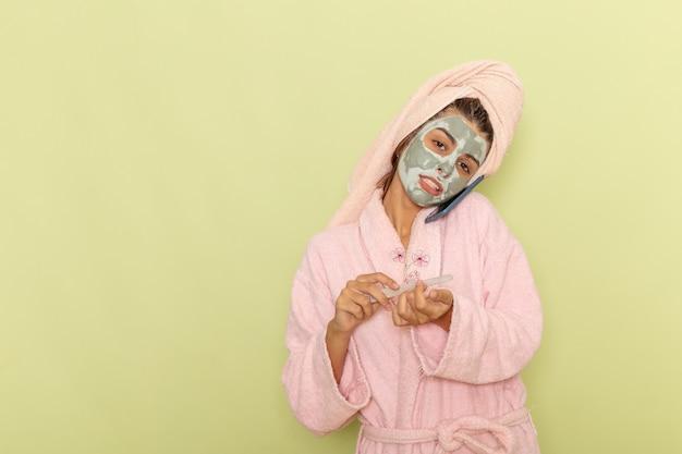 Giovane femmina di vista frontale dopo la doccia in accappatoio rosa, parlando al telefono su una scrivania verde