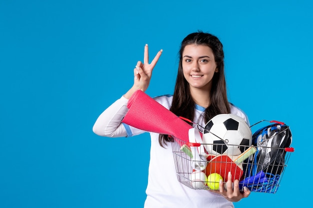 Front view young female after sport shopping blue wall