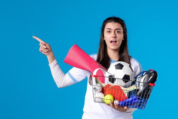 青い壁でスポーツショッピング後の正面図若い女性