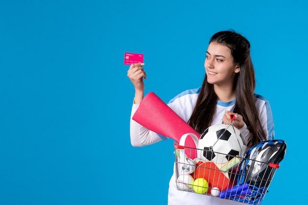 青い壁にクレジットカードでスポーツショッピング後の正面図若い女性