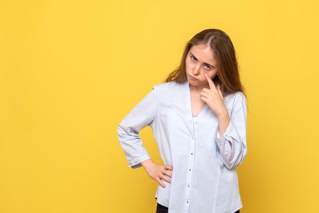 Vista frontale della giovane donna contro il muro giallo