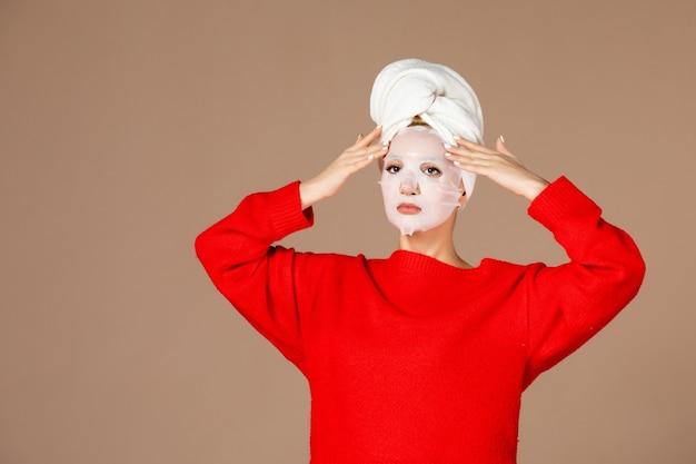 Vista frontale della giovane donna che applica la maschera facciale sul muro marrone