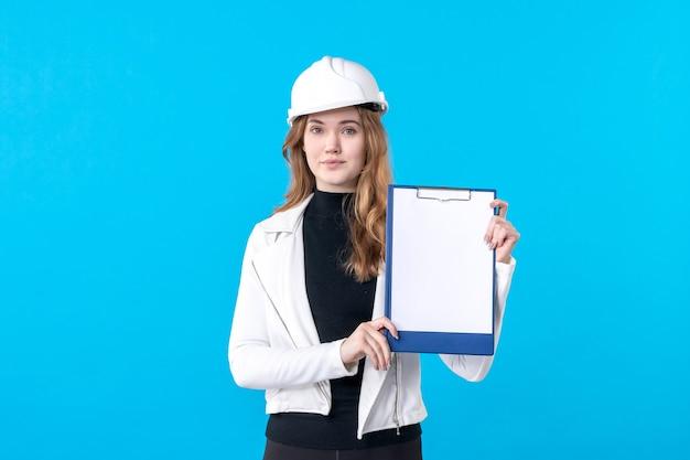 Giovane architetto femminile di vista frontale in casco su blue