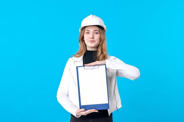 Vista frontale giovane architetto femminile che tiene nota di file sul blue