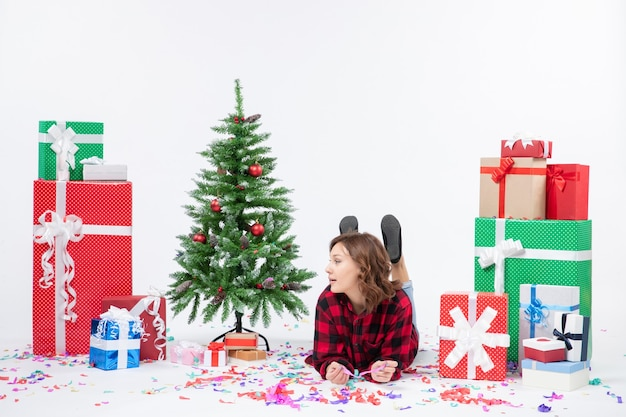 Front view young female around christmas presents and holiday tree laying on white background xmas new year gift color snow