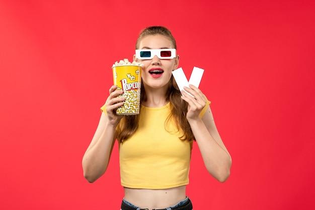 Вид спереди молодая женщина в кино, держащая попкорн и билеты в солнцезащитных очках d на красной стене кинотеатра, женский цвет