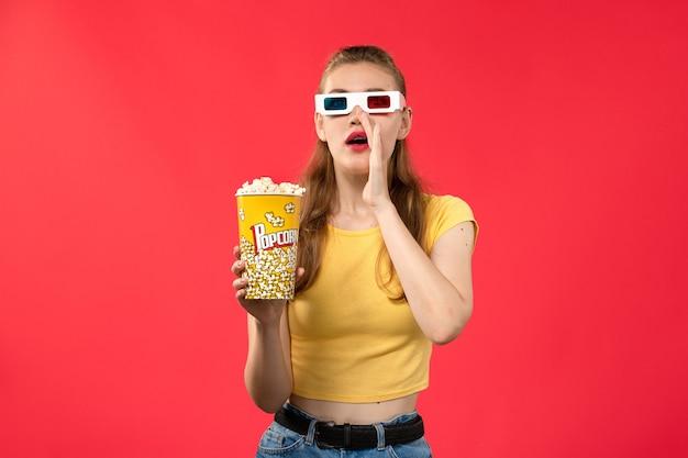 赤い壁の映画館の映画館スナック女性の楽しい映画に-dサングラスでポップコーンを保持している映画館で若い女性の正面図