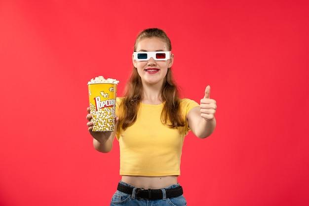 Вид спереди молодая женщина в кинотеатре с попкорном в солнцезащитных очках d на красной стене кинотеатр кинотеатр женщина весело время фильм