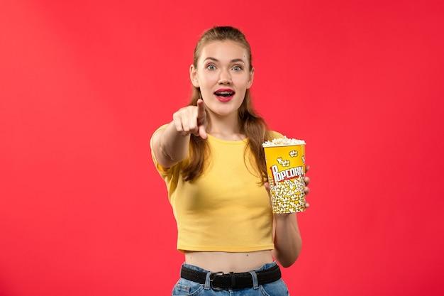 Вид спереди молодая женщина в кинотеатре с попкорном на красной стене кинотеатр кинотеатр женщина весело время фильм