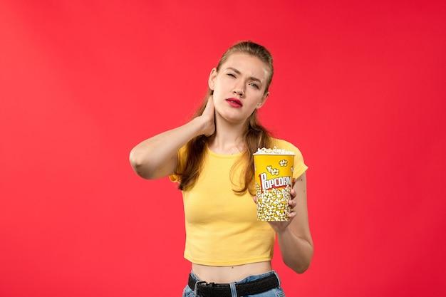 Вид спереди молодая женщина в кино, держащая пакет попкорна и имеющая шейную боль на красной стене кинотеатр кинотеатр женский забавный фильм