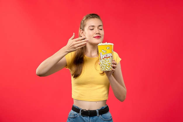 ポップコーンパッケージを保持し、赤い壁の映画館でそれを嗅ぐ映画館で若い女性の正面図劇場映画館女性の楽しい映画