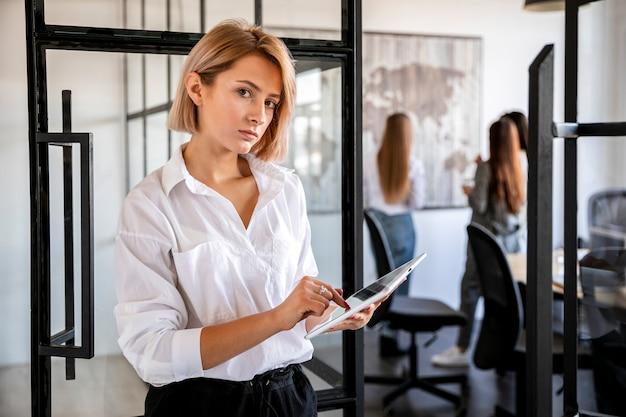 Вид спереди молодая женщина в офисе работает на планшете