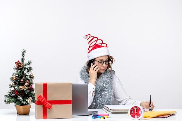 Вид спереди молодая женщина на работе в праздничные дни, разговаривает по телефону на белом фоне