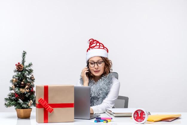 흰색 배경에 노트북을 사용하는 휴일 일 동안 직장에서 전면보기 젊은 여성