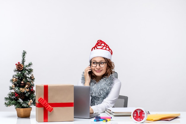 Вид спереди молодая женщина на работе в праздничные дни, используя ноутбук на белом фоне