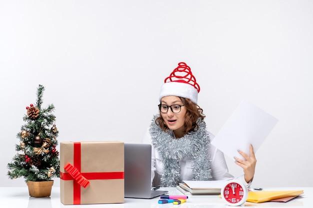 ノートパソコンを使用して白い背景の上のドキュメントを保持している職場で若い女性の正面図