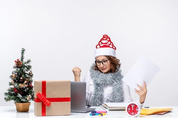Вид спереди молодая женщина на рабочем месте, используя ноутбук и держа документы на белом фоне