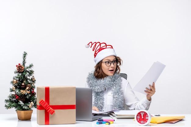 Вид спереди молодая женщина на рабочем месте, работающая с документами на белом фоне
