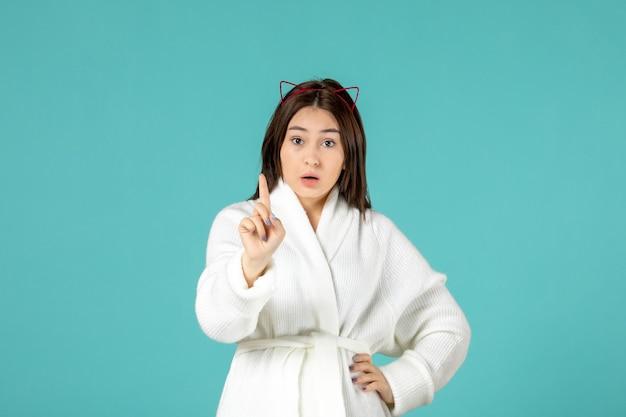 Vista frontale giovane donna in accappatoio e pose diverse su sfondo blu